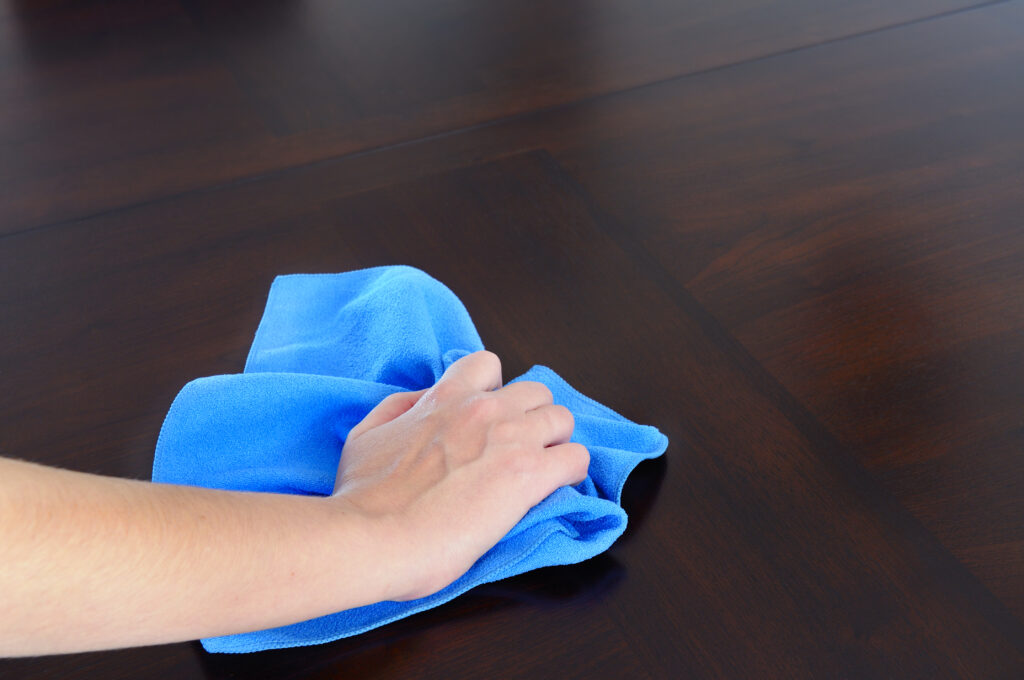 A woman holding a blue cloth cleaning a wooden table.