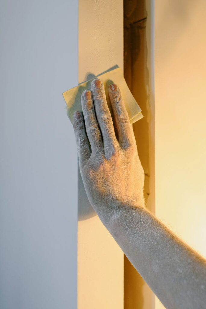 Person using sandpaper on the wall